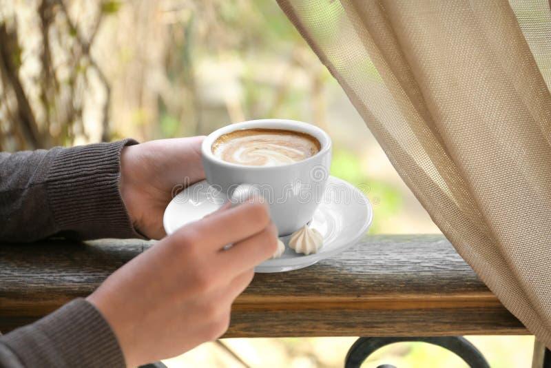有杯子的少妇在窗口附近的可口咖啡 库存图片