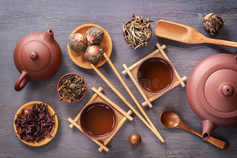 有杯子的布朗陶瓷茶壶在特别木立场,茶道的各种各样的属性,各种各样绿茶 库存图片