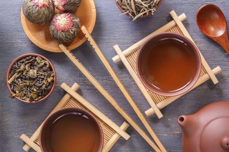 有杯子的布朗陶瓷茶壶在特别木立场,茶道的各种各样的属性,各种各样绿茶 库存照片