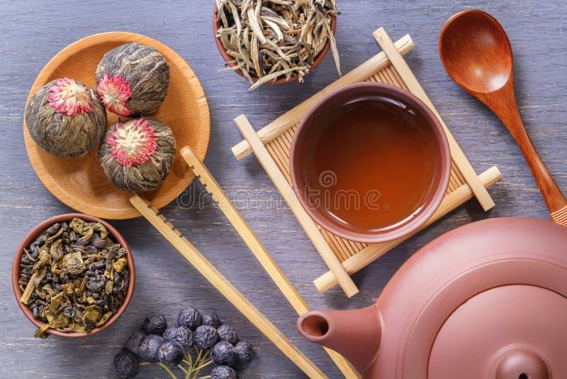 有杯子的布朗陶瓷茶壶在特别木立场,茶道的各种各样的属性,各种各样绿茶 免版税库存图片