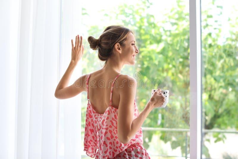 有杯子的年轻愉快的妇女在窗口附近的芳香咖啡在家 库存图片