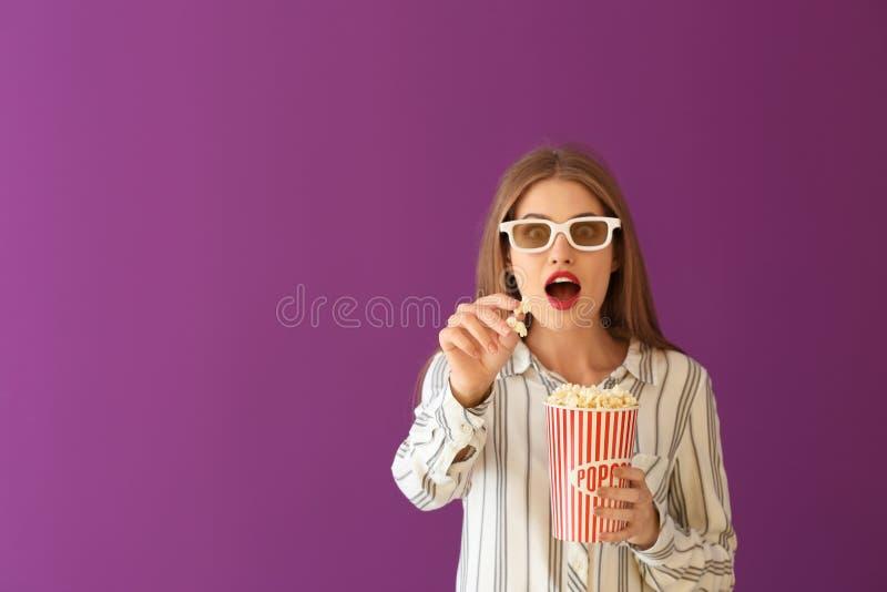 有杯子的情感年轻女人在颜色背景的玉米花和3D戏院玻璃 图库摄影