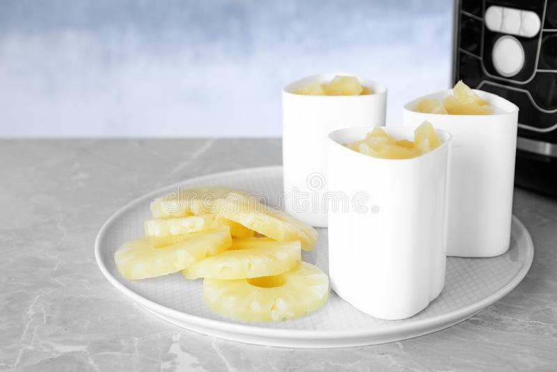 有杯子的盘子在桌上的酸奶和菠萝切片 多烹饪器材食谱 免版税库存图片