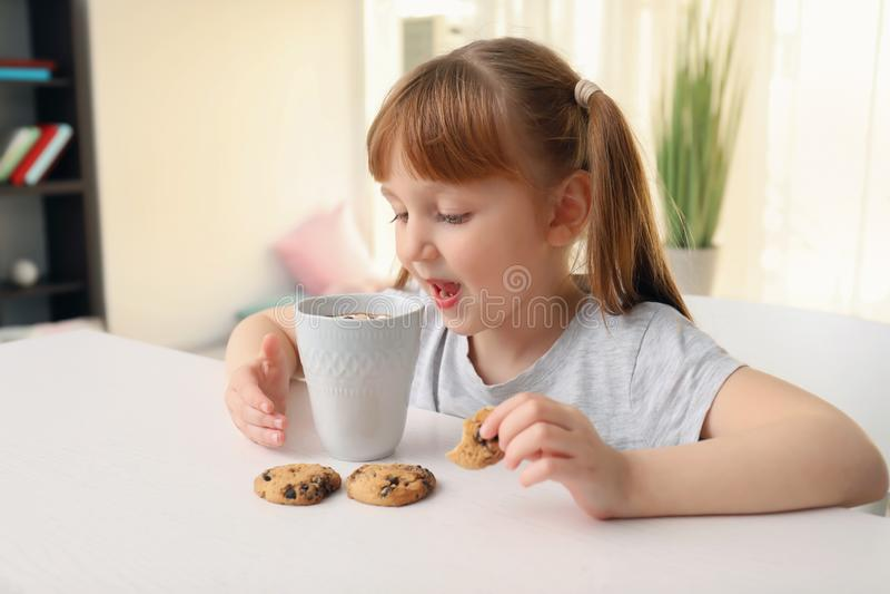 有杯子的逗人喜爱的女孩热的可可粉饮料和曲奇饼在家 免版税库存照片