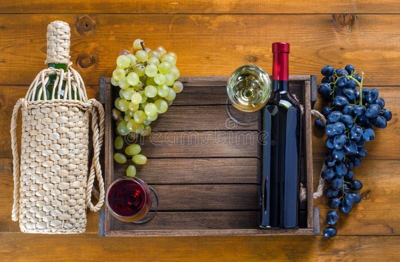 有杯的两个瓶酒和葡萄在木背景 图库摄影