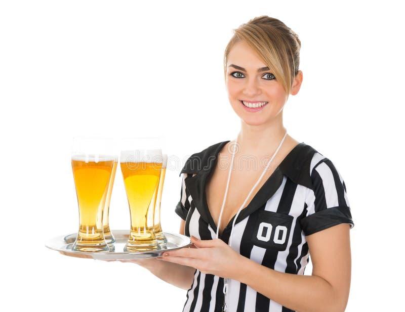 有杯的女性裁判员啤酒 库存图片
