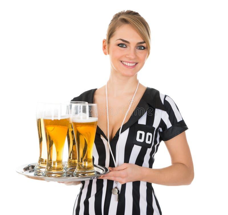 有杯的女性裁判员啤酒 库存照片
