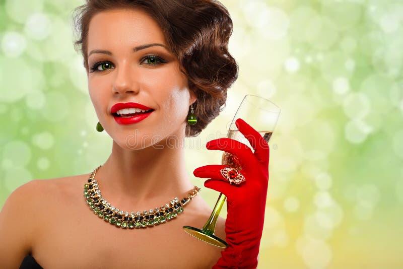 有杯的性感的式样女孩在党,在假日发光的背景的饮用的香槟的香槟 免版税库存图片