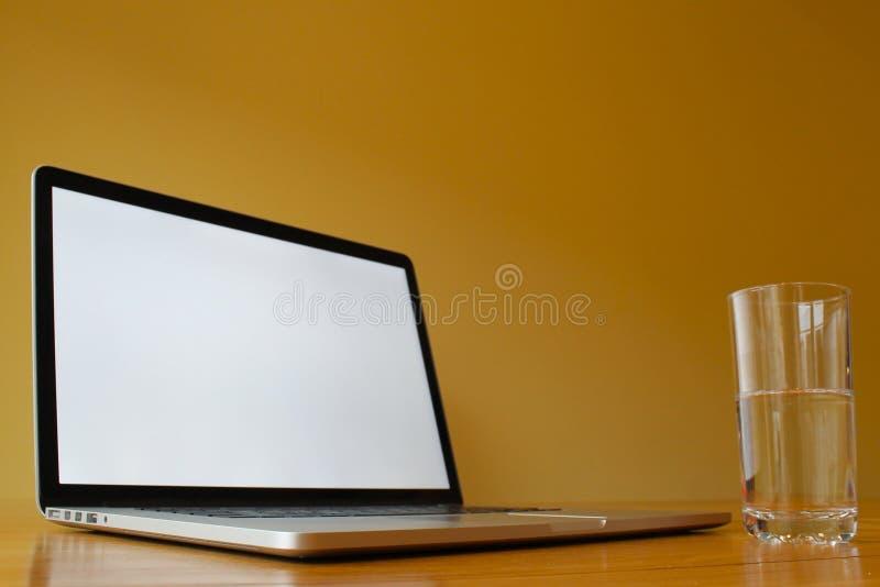 有杯的空白的膝上型计算机水 免版税库存照片
