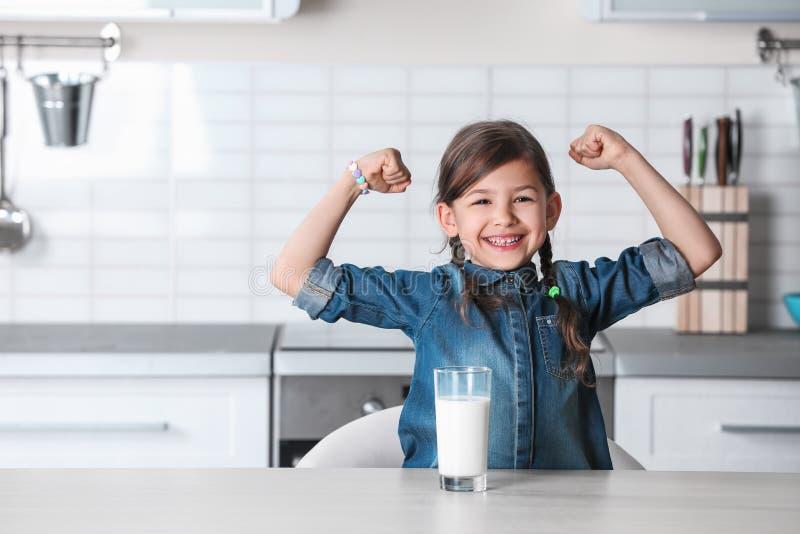 有杯的逗人喜爱的女孩牛奶在桌上在厨房里 免版税库存图片