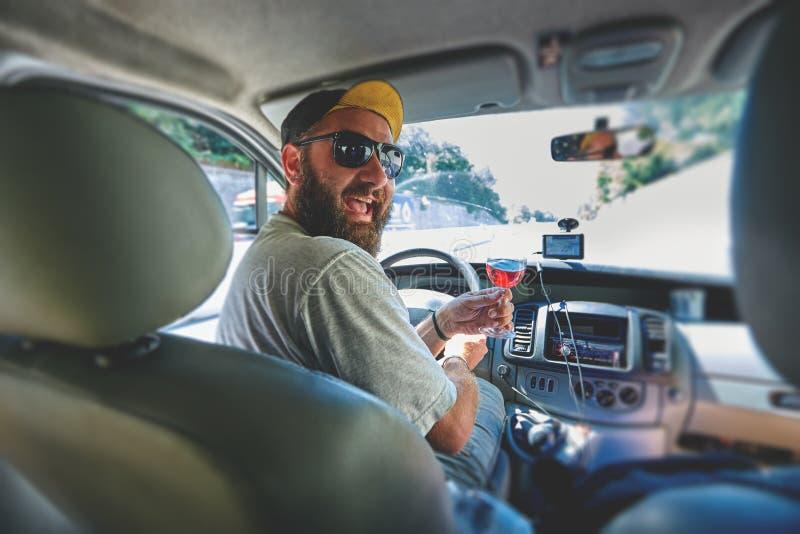 有杯的滑稽的微笑的刮胡须的人在汽车的藤 免版税库存照片