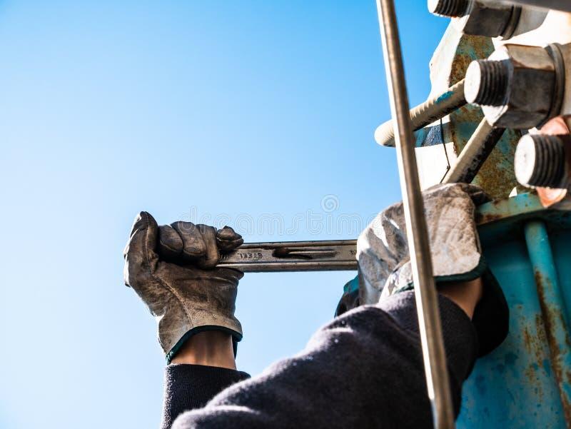有板钳的工作者在高度,当维护阀门时 免版税库存图片