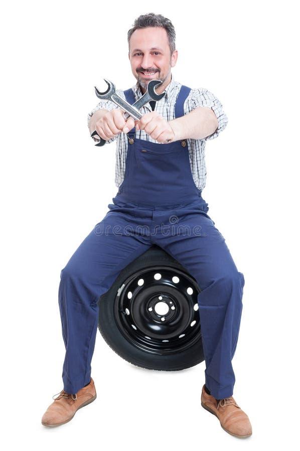 有板钳的微笑的英俊的技工坐轮胎 免版税库存照片