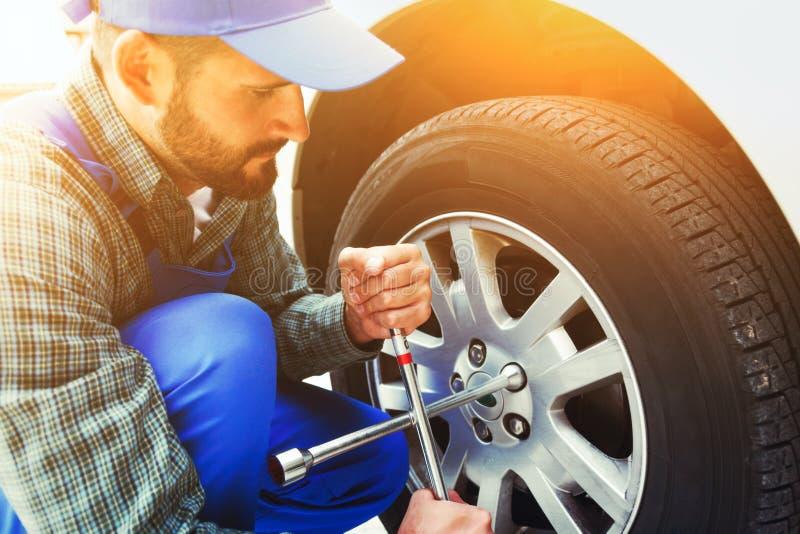 有板钳的技工改变的车胎 图库摄影
