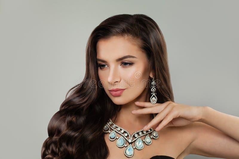 有构成、发光的头发和豪华钻石项链的逗人喜爱的深色的妇女 免版税库存图片