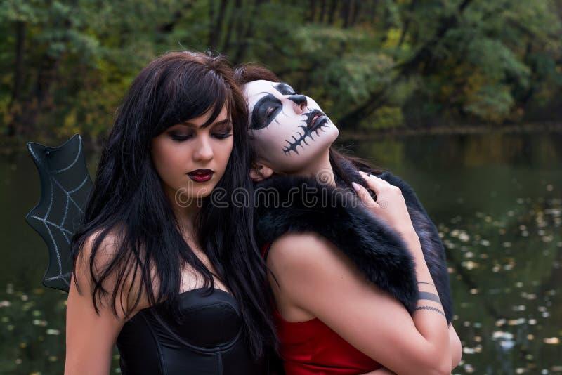 有构成的两名年轻浅黑肤色的男人妇女喜欢万圣夜头骨和 库存图片