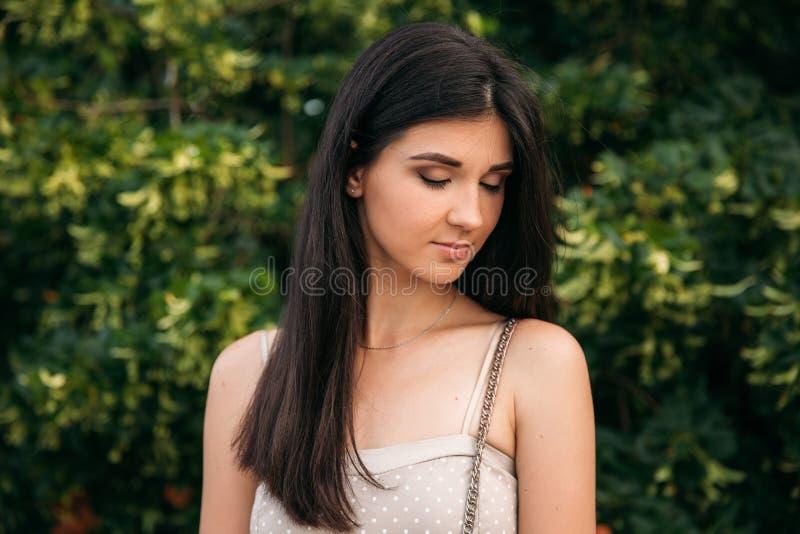 有构成的深色的女孩在绿色背景前面站立 免版税库存图片