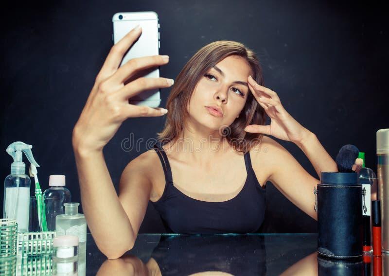 有构成的秀丽妇女 看手机和做selfie照片的美丽的女孩 免版税库存图片