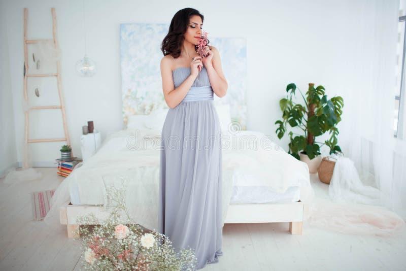 有构成的逗人喜爱的女孩在站立在床旁边的一件蓝色晚礼服 美好的舒适内部在背景中 免版税图库摄影