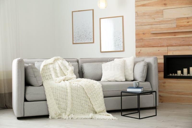 有枕头和格子花呢披肩的舒适沙发在装饰壁炉附近 r 库存照片