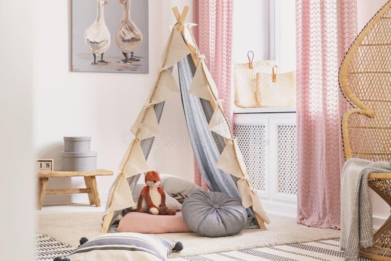 有枕头和玩具的帐篷在儿童的游戏室中间在现代房子,真正的照片里 免版税库存照片