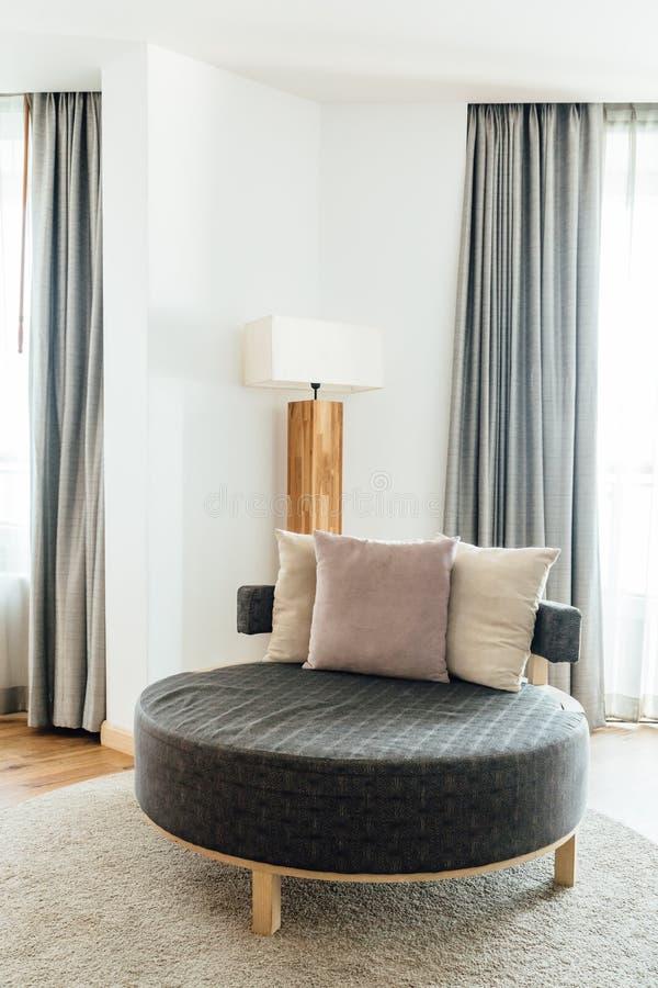 有枕头的圈子沙发在用明亮和温暖的口气装饰的主卧室 免版税库存照片