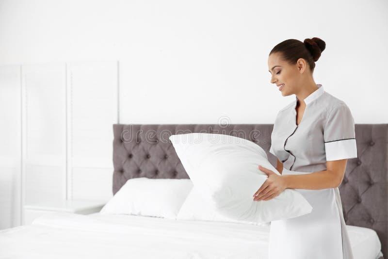 有枕头的年轻女服务生在酒店房间 库存图片