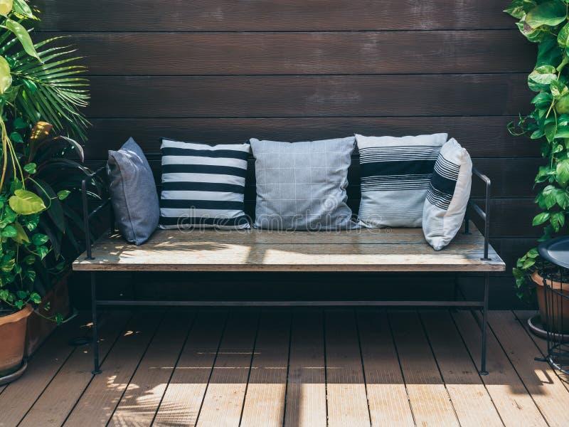 有枕头的木沙发在赤土陶器罐的绿色热带树之间在木墙壁背景 库存图片