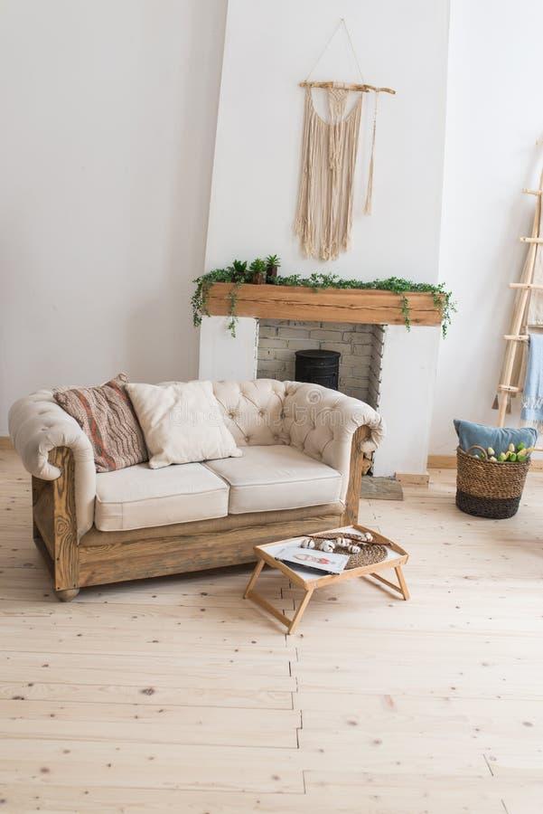 有枕头的米黄沙发在壁炉附近 一张小咖啡桌 客厅的内部 免版税库存图片