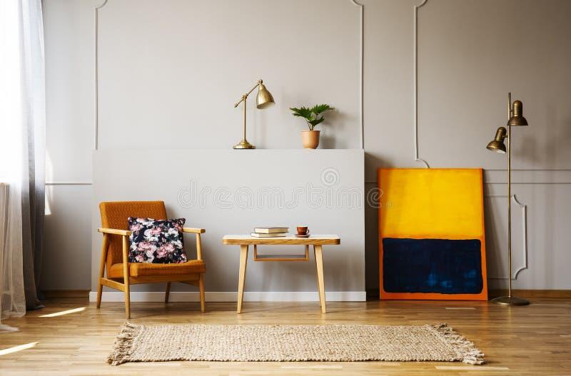 有枕头的葡萄酒橙色扶手椅子在与书和蓝色和橙色绘画的咖啡桌旁边 免版税库存图片