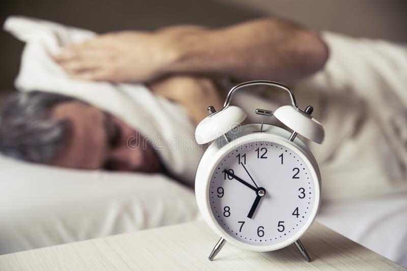有枕头的困年轻人覆盖物耳朵,他在床上看闹钟 免版税库存照片
