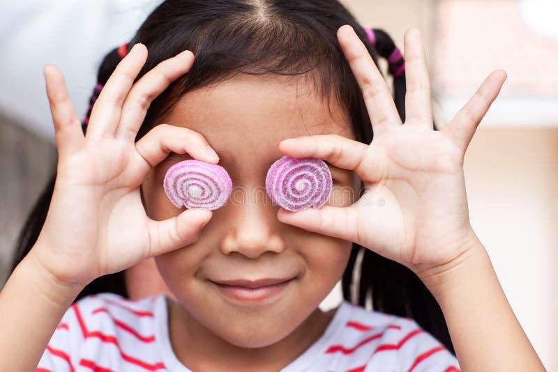 有果冻糖果微笑的逗人喜爱的亚裔儿童女孩 免版税库存图片