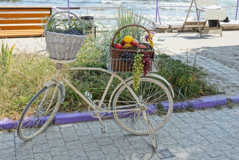 有果子和植被篮子的白色老自行车在边路站立在海附近 免版税库存照片