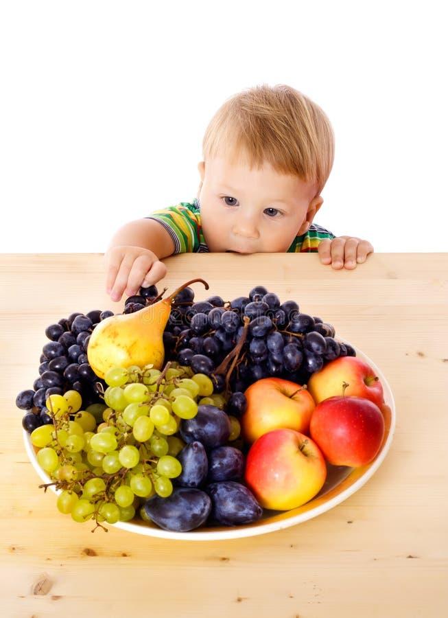 有果子盘的婴孩  库存照片
