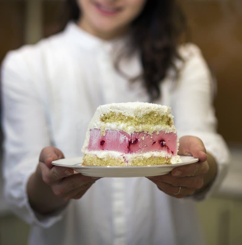 有果子饼干白色和桃红色乳脂状的蛋糕新可口美味的自创片断的年轻有吸引力的微笑的妇女藏品板材  库存照片