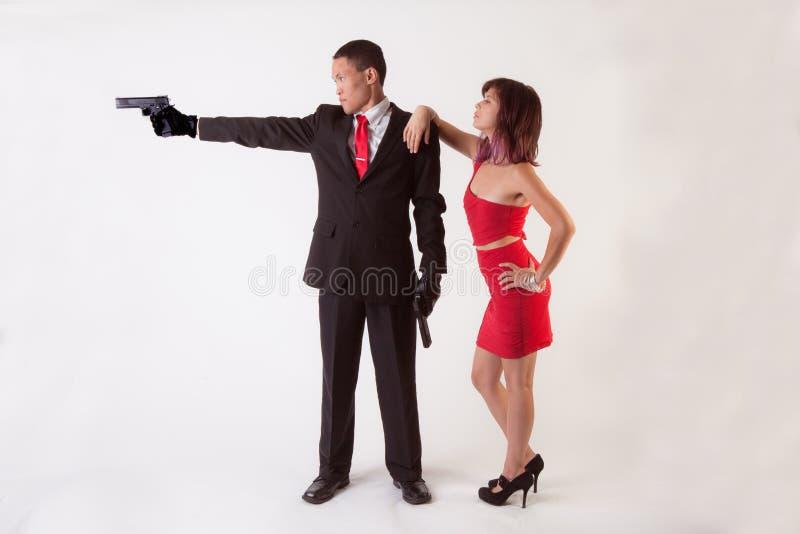 有枪和可爱的妇女的人 库存图片