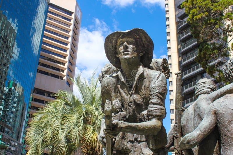 有枪和手榴弹的澳大利亚士兵站立在现代高层建筑物之间在纪念品给CBD的布里斯班Qu澳大利亚士兵 免版税图库摄影