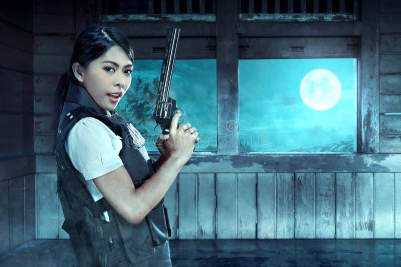 有枪的亚裔女警在他的在老无盖货车里面的手手表 免版税库存图片