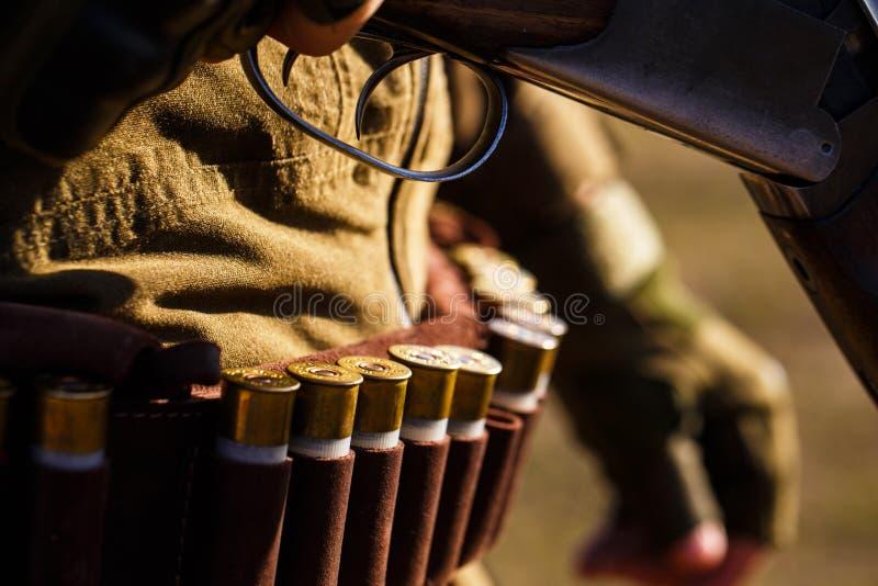 有枪的弹药,弹药筒 猎人人 人充电一杆寻找的步枪 人是在狩猎 ?? 免版税图库摄影