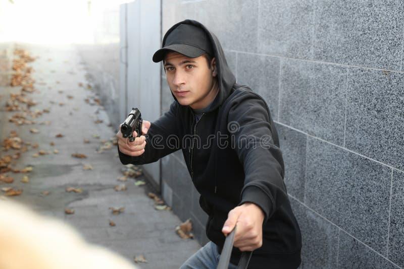 有枪的男性窃贼窃取从受害者的袋子户外 免版税库存图片