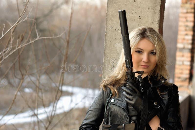 有枪的美丽的女孩 免版税库存照片