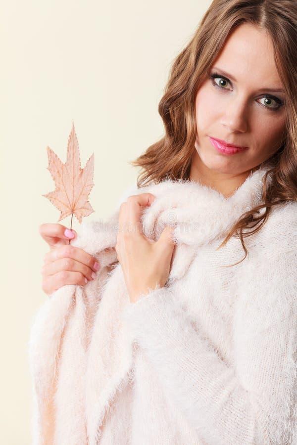 有枫叶的俏丽的秋季女孩在手中 免版税库存图片