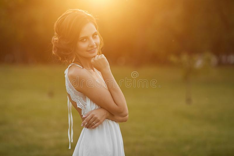 有柔和的构成的美丽和年轻深色的式样女孩,在短的白色礼服立场和摆在绿色公园  免版税图库摄影