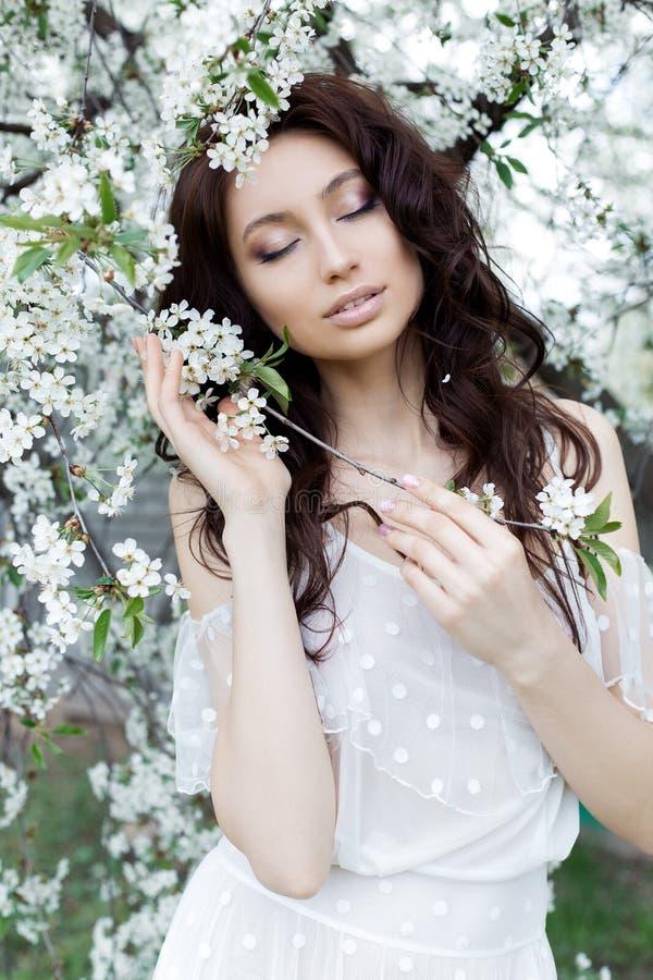 有柔和的眼睛构成充分的嘴唇的美丽的逗人喜爱的甜性感的女孩新娘在白光礼服在温暖的s的繁茂花园里走 免版税库存图片