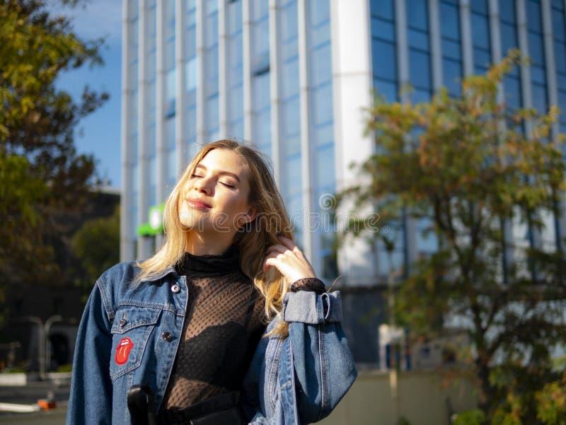 有柔滑的头发的可爱的女孩在一个现代大厦的背景在一明亮的天 库存照片