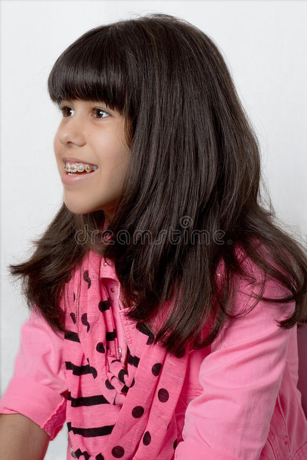 有柔滑的头发的年轻拉丁女孩&上色了括号 库存图片