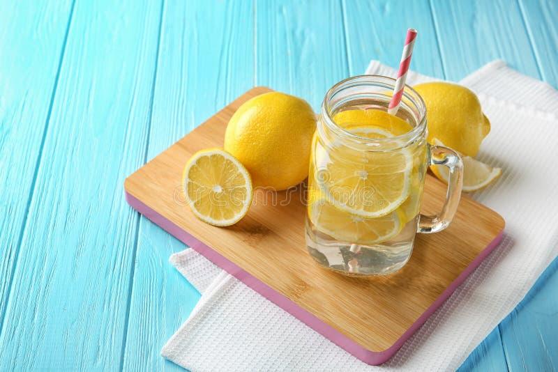 有柠檬水和新鲜水果的金属螺盖玻璃瓶 图库摄影