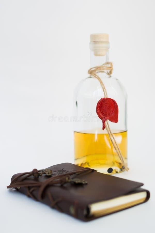 有柠檬酒精的玻璃瓶在白色背景 有白色板料的棕色皮革笔记本 免版税库存照片