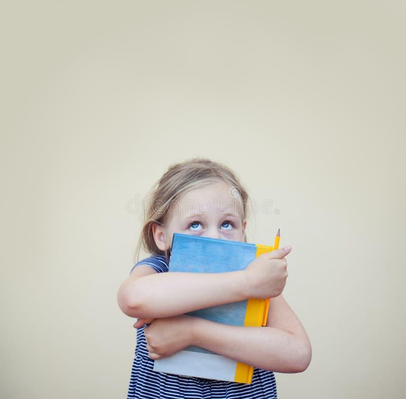 有查寻在与拷贝空间的背景的书的滑稽的儿童女孩 库存照片