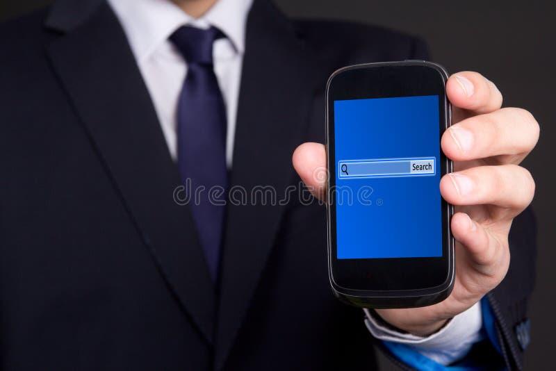 有查寻酒吧的手机在屏幕上在商人手上 库存图片